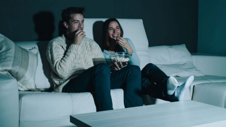Paar schaut sich mit Popcorn einen Film an