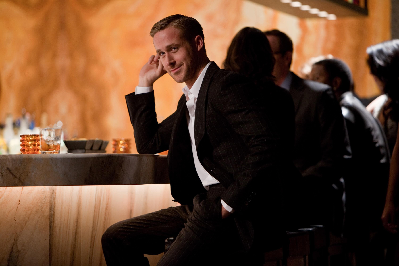 Mann sitzt im schwarzen Anzug an der Bar