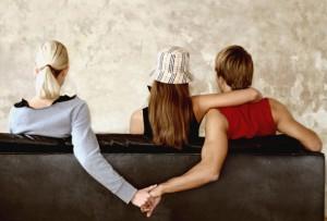 Dreiecksbeziehung, Mann hält Hand von anderer Frau