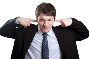 Mann im Anzug hält sich Ohren zu