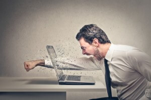 Mann ist wütend und schlägt durch Laptop