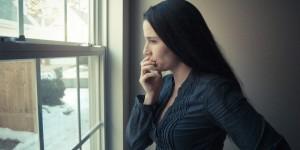 Frau mit Liebeskummer schaut traurig aus Fenster