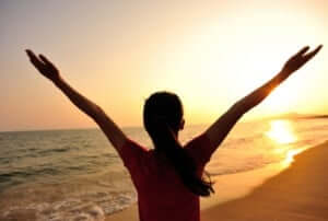 Frau befreit am Strand mit Arme nach oben